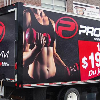 Wrap commercial sur un camion cube de Pro Gym servant de panneau publicitaire pour les promotions